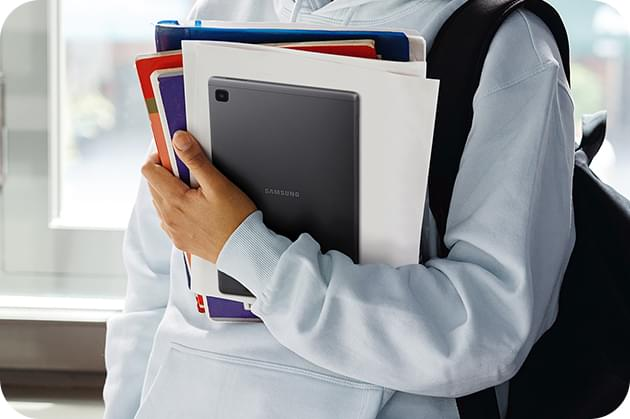 Student holding Galaxy Tab A7 Lite 4G amongst their reading materials in their arms