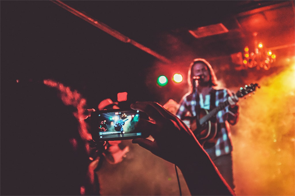 Person recording a live concert with his phone