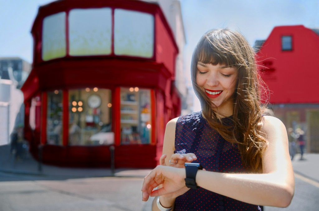 Lady in the street interacting with her smartwatch
