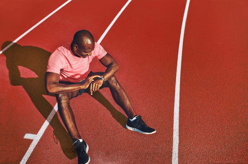 Athlete on running track looking at his smartwatch