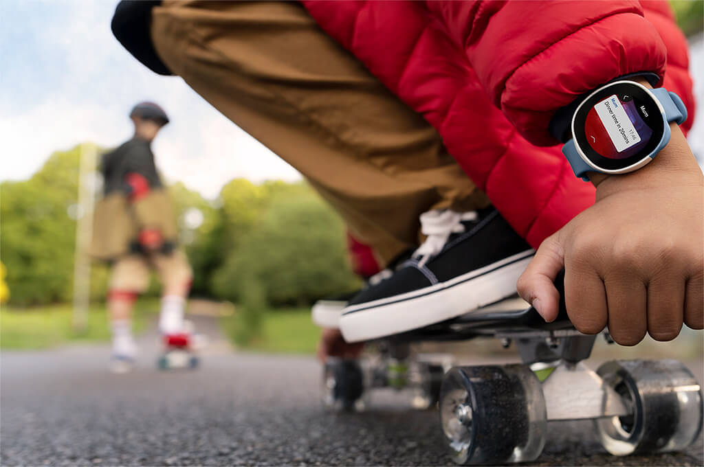 Child skateboarding and wearing a Neo smartwatch