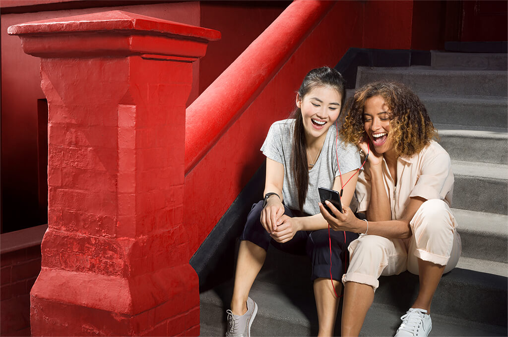 Two girls sitting together looking at a phone