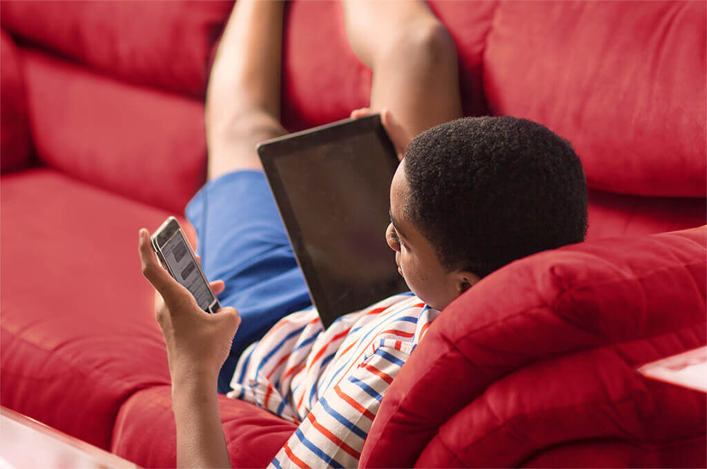 Child using a phone and tablet