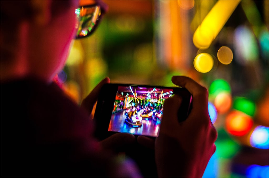 Teenager taking a picture at a fairground