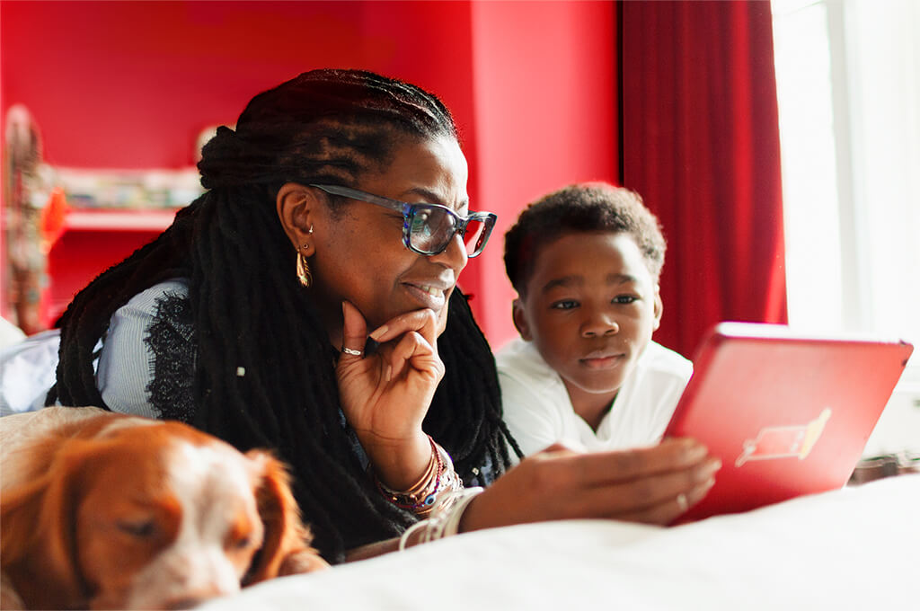 Mother and son looking at red laptop