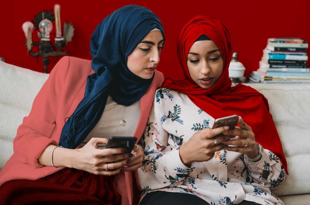 Two ladies sitting on the couch looking at their mobile phones